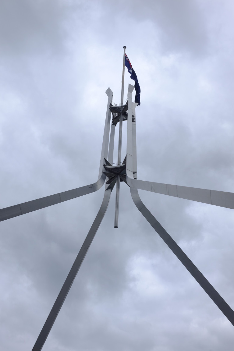 looking up to parliament house flag from roof of the building