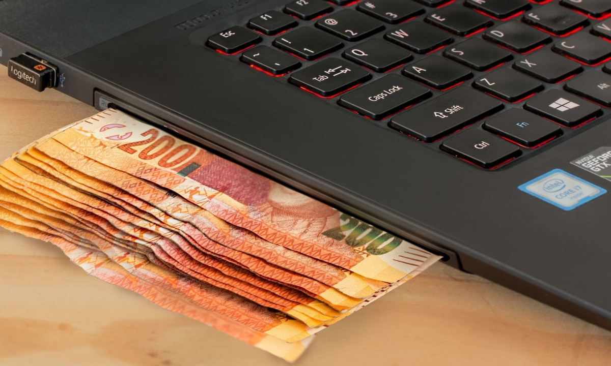 laptop with currency underneath