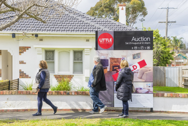 people walking past a house after auction
