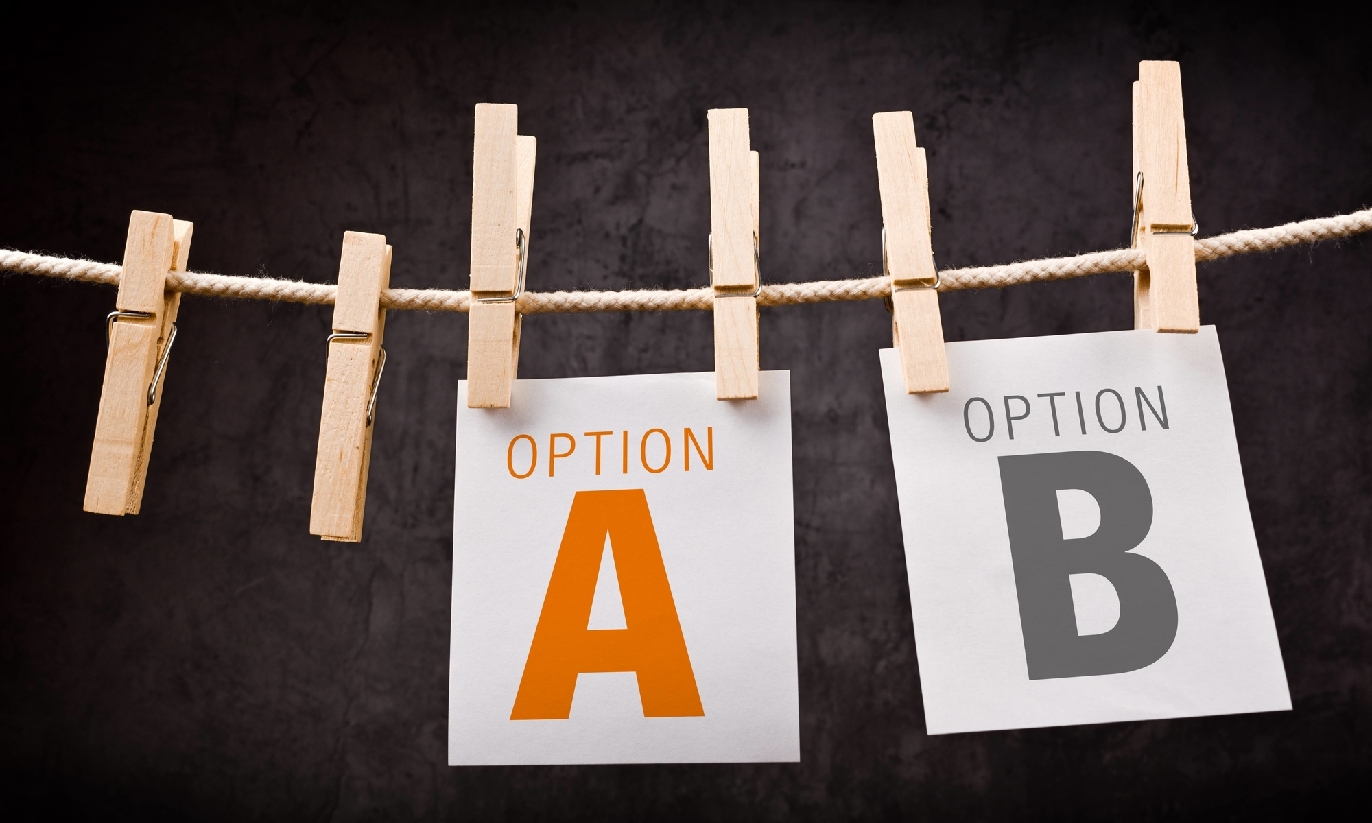 Concept of choice between two options marked as A and B. Letters are printed on note paper and attached to rope with clothes pins.