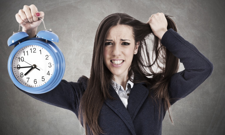 woman holding clock and tearing hair